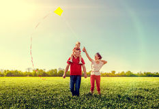 Family running with a kite. Royalty Free Stock Image
