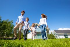 Family running on lawn near house. Happy family with children running on lawn near their house Stock Photo