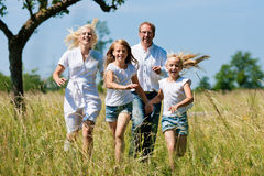 Family running in the meadow Royalty Free Stock Image