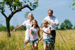 Family running in the meadow Royalty Free Stock Photos