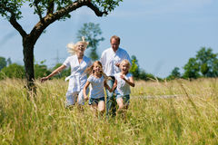 Family running in the meadow Royalty Free Stock Images