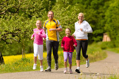 Family running in the meadow for sport. Happy Family with two girls running or jogging for sport and better fitness in a meadow in summer royalty free stock photography