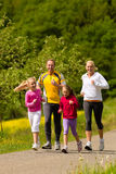 Family running in the meadow for sport. Happy Family with two girls running or jogging for sport and better fitness in a meadow in summer Royalty Free Stock Images