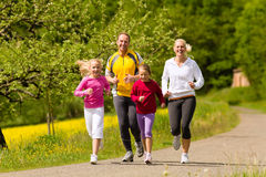 Family running in the meadow for sport. Happy Family with two girls running or jogging for sport and better fitness in a meadow in summer Royalty Free Stock Photo