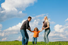 Family running on meadow in summer Stock Images