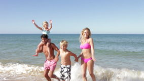 Family Running Out Of Sea stock video footage