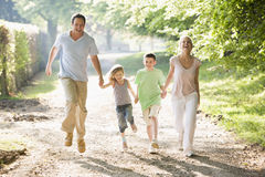 Family running outdoors holding hands and smiling Royalty Free Stock Photos