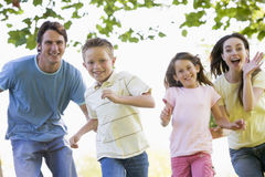 Family running outdoors smiling Stock Image