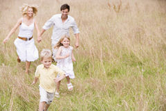Family running outdoors smiling Stock Photos