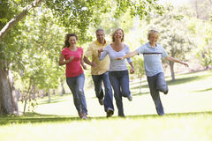 Family Running Through A Park Royalty Free Stock Photos