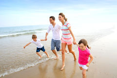 Family running on a sandy beach Royalty Free Stock Photo