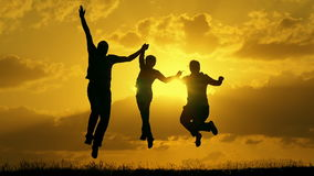 Family running at sunset and jumping up raising their hands winners