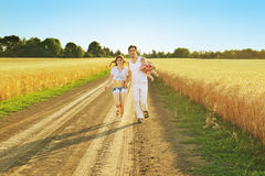 Family Running Together Through Summer Harvested Field. Happy family enjoying and running together outdoors. Royalty Free Stock Photography