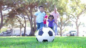 Family Running Towards Soccer Ball And Kicking It. Soccer ball resting on grass as family run towards it before boy kicks it. Shot on Canon 5d Mk2 with a frame stock video footage