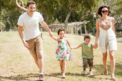 Family running with two young children. At the park stock photos