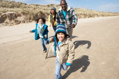 Family Running On Winter Beach Stock Photo