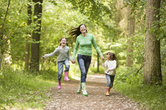 Family Running Through Woods Stock Photo