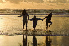 Family runs in the surf at sunset. Stock Photography