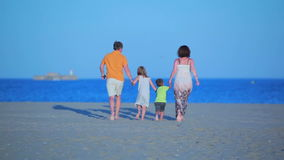 Family runs to sea on the beach stock video footage