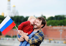 Family with russian flag with Moscow Kremlin on background Stock Photos