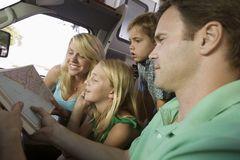 Family in RV Looking at Road Map Stock Photography
