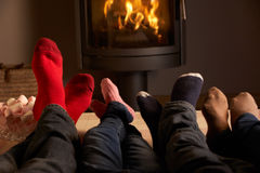 Family's Feet Relaxing By Cosy Log Fire. Close Up Of Family's Feet Relaxing By Cosy Log Fire With Marshmallows Royalty Free Stock Image