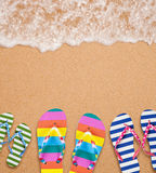 Family's flip flop pairs on sea surf with copy space Stock Photos