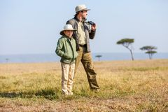 Family safari in Africa. Family of father and child on African safari vacation enjoying bush view royalty free stock photos