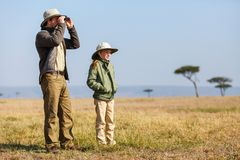 Family safari in Africa. Family of father and child on African safari vacation enjoying bush view royalty free stock photo