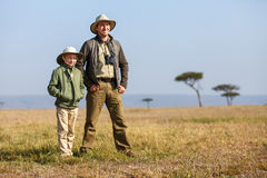 Family safari in Africa. Family of father and child on African safari vacation enjoying bush view royalty free stock photography