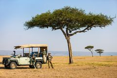 Family safari. Family of father and kids on African safari vacation enjoying morning game drive stock image