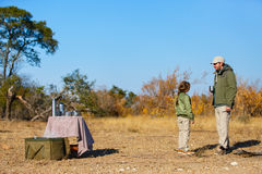 Family safari. Family of father and child on African safari vacation enjoying bush breakfast royalty free stock images