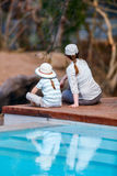 Family safari. Family of mother and child on African safari vacation enjoying wildlife viewing sitting near swimming pool royalty free stock photos