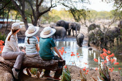 Family safari. Family of mother and kids on African safari vacation enjoying wildlife viewing at watering hole Stock Photography