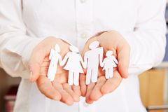 Family safe in two hands. Paper family protected safe in two female hands Royalty Free Stock Image