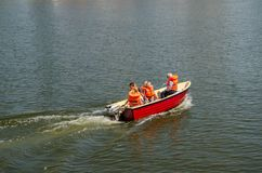 A family sail in a boat in orange life jackets. River in Wroclaw stock image