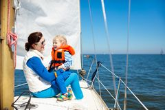 Family sailing. Mother and child on sea sail yacht. Mother and baby boy sail on yacht in sea. Family sailing on boat. Mom and kid in safe life jacket travel on Royalty Free Stock Images