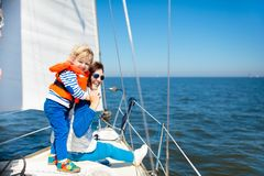 Family sailing. Mother and child on sea sail yacht. Mother and baby boy sail on yacht in sea. Family sailing on boat. Mom and kid in safe life jacket travel on Stock Photo