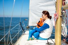 Family sailing. Mother and child on sea sail yacht stock photo