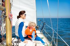 Family sailing. Mother and child on sea sail yacht. Mother and baby boy sail on yacht in sea. Family sailing on boat. Mom and kid in safe life jacket travel on stock photography