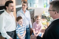 Family and sales man in kitchen showroom stock photos