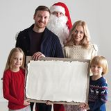 Family and Santa Claus. Christmas portrait of happy smiling family with two children and Santa Claus embracing them holding blank vintage paper Royalty Free Stock Image