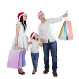 Family with santa hat and shopping bags Royalty Free Stock Photos