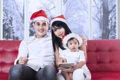 Family with santa hat sitting on sofa Royalty Free Stock Photo