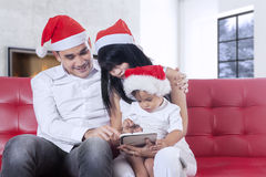 Family with santa hat using tablet on sofa Royalty Free Stock Photos