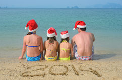 Family in santa hats having fun on beach Royalty Free Stock Images