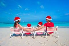 Family in santa hats having fun on tropical beach Royalty Free Stock Image