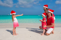 Family in santa hats having fun on tropical beach Stock Photography