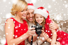 Family in santa helper hats looking at pictires Royalty Free Stock Images