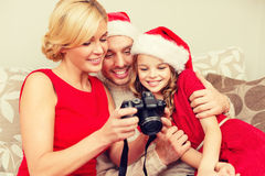 Family in santa helper hats looking at pictires Royalty Free Stock Photos